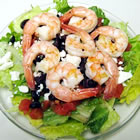 greek-style shrimp salad on a bed of baby spinach picture