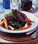 chicken in red wine sauce with root vegetables and wilted greens picture