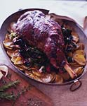 roast leg of lamb on a bed of potatoes and wilted greens picture